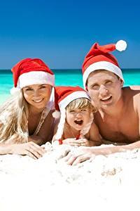 Фотографии Мужчины Новый год Море Пляжа Три Песка В шапке девушка Дети