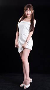 Картинка Азиатки На черном фоне Позирует Платье Ноги Взгляд молодые женщины