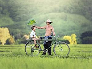 Картинка Азиаты Мужчины Траве 2 Велосипеды Мальчик Сидящие Улыбается