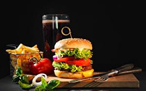 Фотографии Гамбургер Картофель фри Ножик Овощи Пиво Черный фон Разделочная доска Вилка столовая Стакане Еда