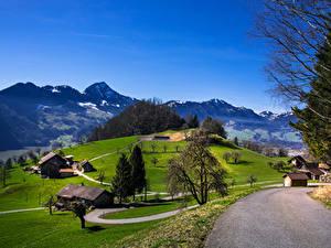 Картинка Швейцария Горы Дороги Луга Здания Деревья Schwyz Природа