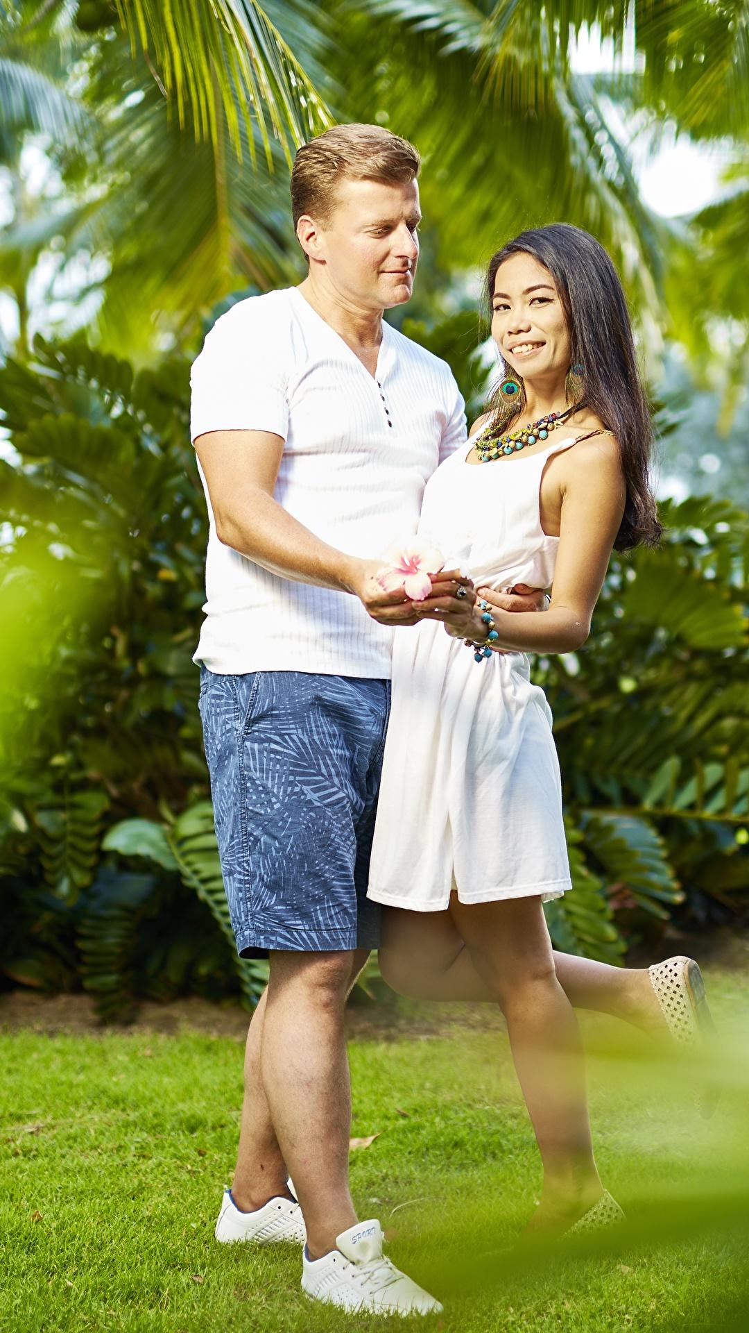 Фотографии мужчина Влюбленные пары улыбается 2 Объятие молодые женщины азиатка Шорты 1080x1920 для мобильного телефона Мужчины любовники Улыбка два две Двое вдвоем девушка Девушки обнимает обнимаются молодая женщина Азиаты азиатки шорт шортах