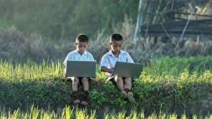 Фотографии Азиаты Мальчики Трава 2 Сидящие Ноутбуки Ребёнок