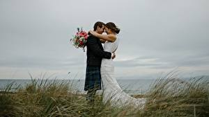 Обои Влюбленные пары Букет Мужчины Трава 2 Брак Жених Невеста Обнимаются молодая женщина
