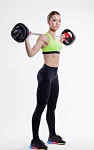 Картинки Фитнес Серый фон Шатенки Тренировка Штангой Униформе Девушки Спорт