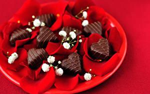 Фотографии День всех влюблённых Сладости Конфеты Шоколад Красном фоне Сердца Лепестки Еда