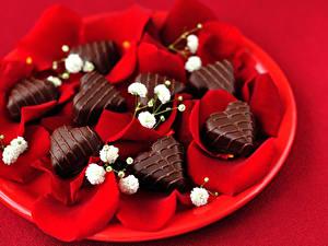 Фотографии День всех влюблённых Сладости Конфеты Шоколад Красном фоне Сердца Лепестки