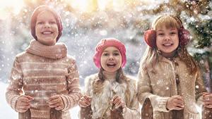 Картинка Зимние Трое 3 Мальчишка Девочки Снега Улыбка Свитере Шапка ребёнок