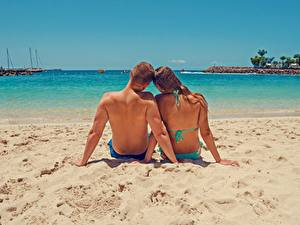 Картинка Влюбленные пары Мужчины Море Пляжи Песок Сзади Двое Сидит Спины Отдых девушка