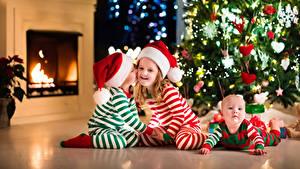 Картинка Рождество Мальчишки Девочки Грудной ребёнок Втроем В шапке Новогодняя ёлка Камин ребёнок