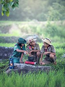 Картинка Камень Азиатки Скаут Униформе Траве Три Шляпа Мальчишки ребёнок