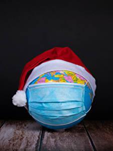 Обои для рабочего стола Рождество Коронавирус Маски Доски Черный фон Глобусы В шапке