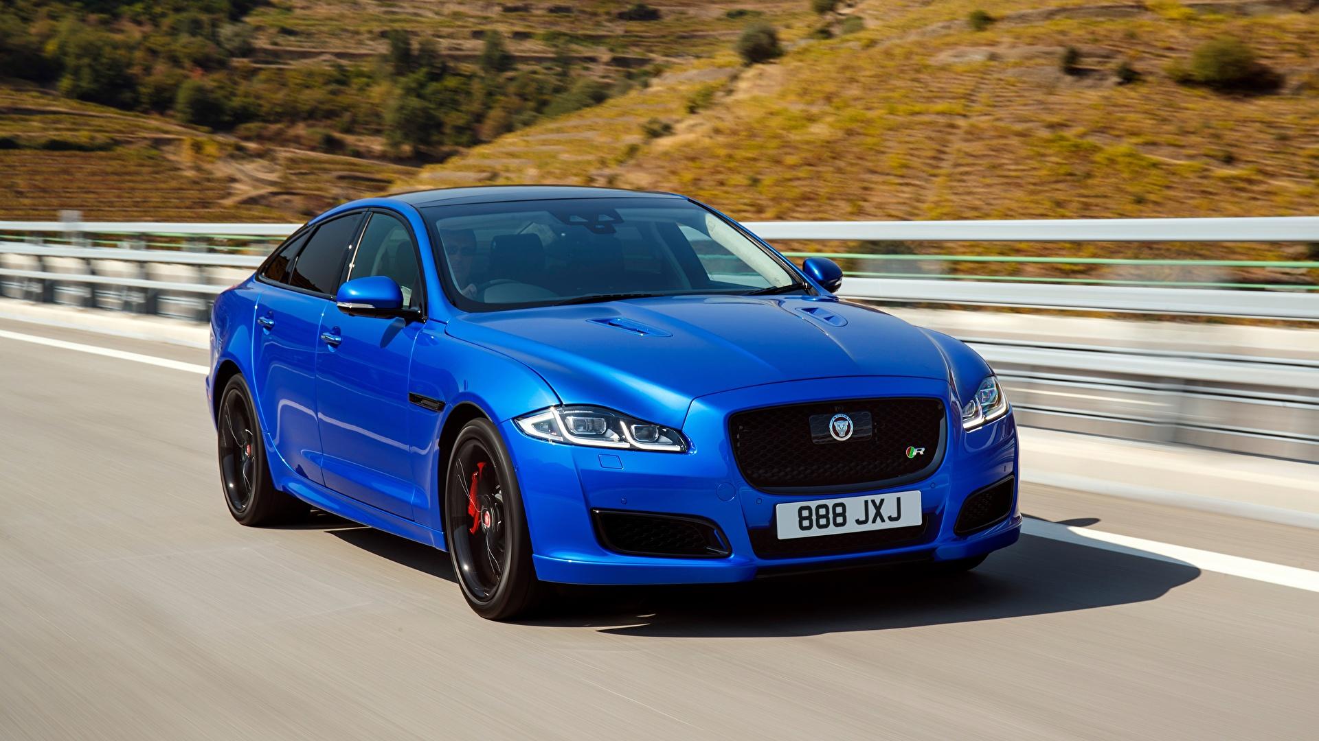 Фотография Ягуар боке Седан синяя скорость машина 1920x1080 Jaguar Размытый фон Синий синие синих едет едущий едущая Движение авто машины Автомобили автомобиль