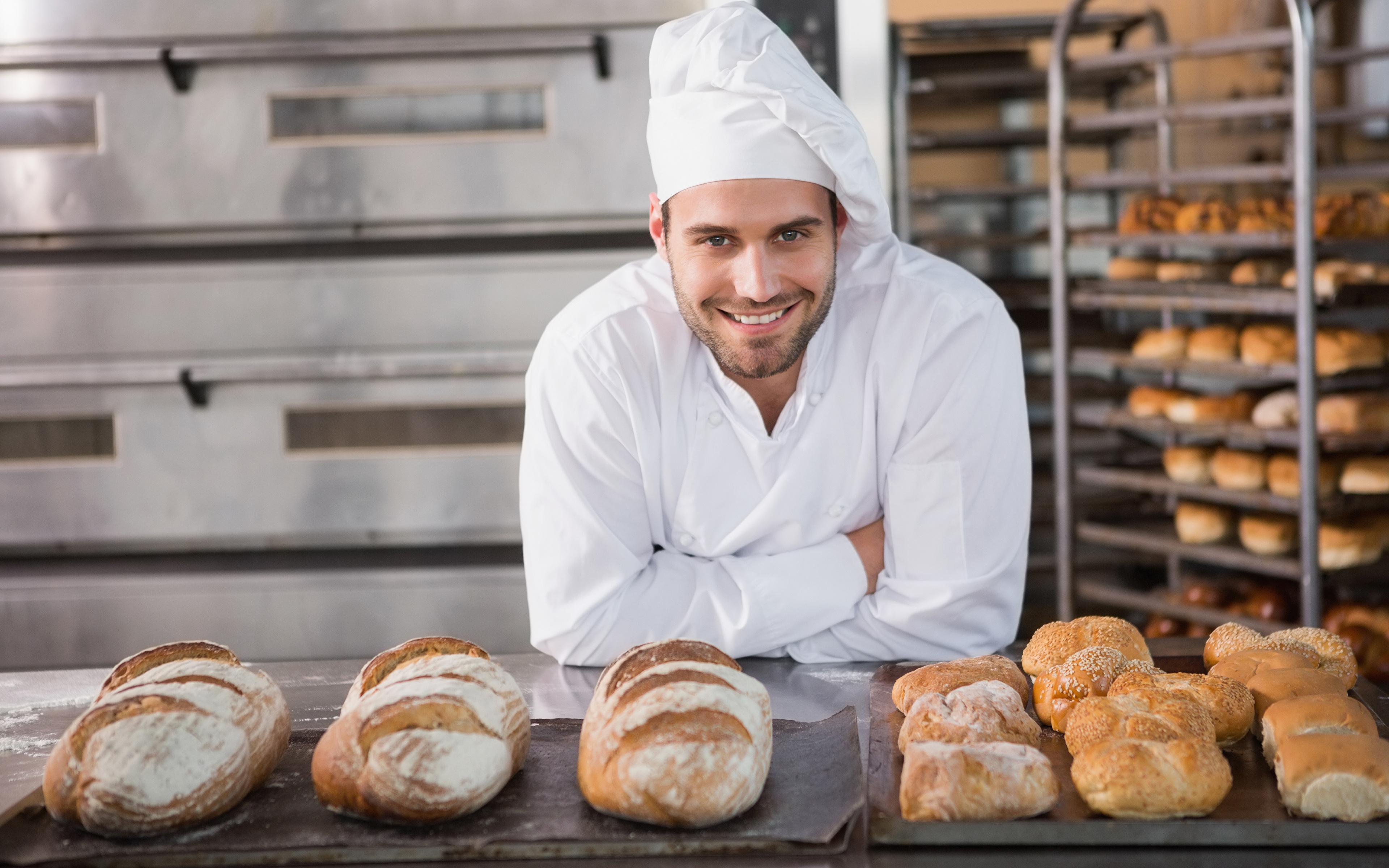 Мужчина повар хлеб улыбается