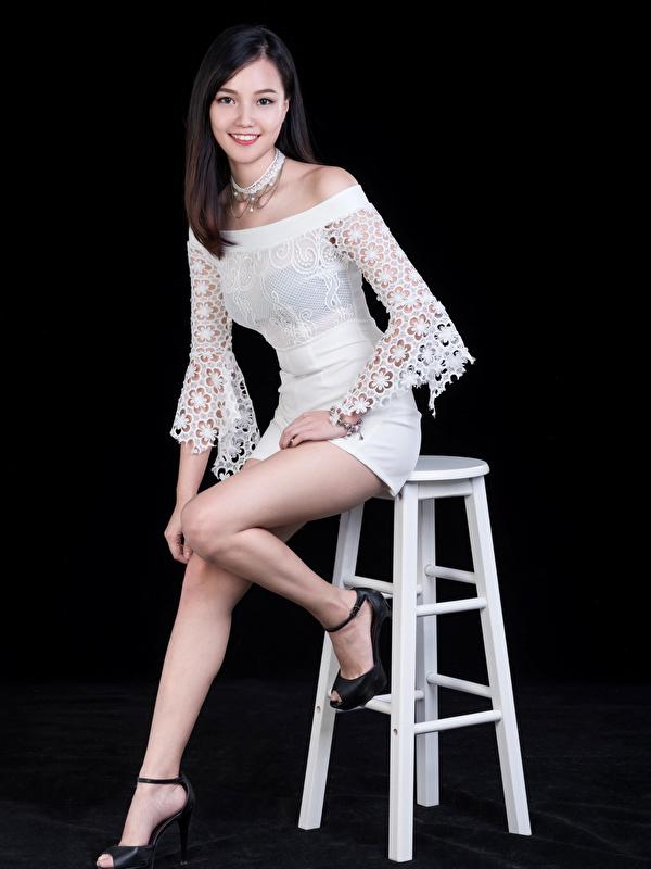 Фото Улыбка позирует Девушки Ноги азиатки смотрит на черном фоне Платье 600x800 для мобильного телефона улыбается Поза девушка молодая женщина молодые женщины ног Азиаты азиатка Взгляд смотрят Черный фон платья