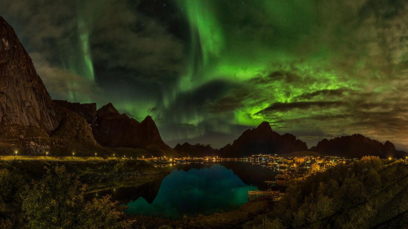 Фотографии Норвегия Reine Полярное сияние гора Природа Небо Озеро Ночь облачно 1366x768 северное сияние Горы ночью в ночи Ночные облако Облака
