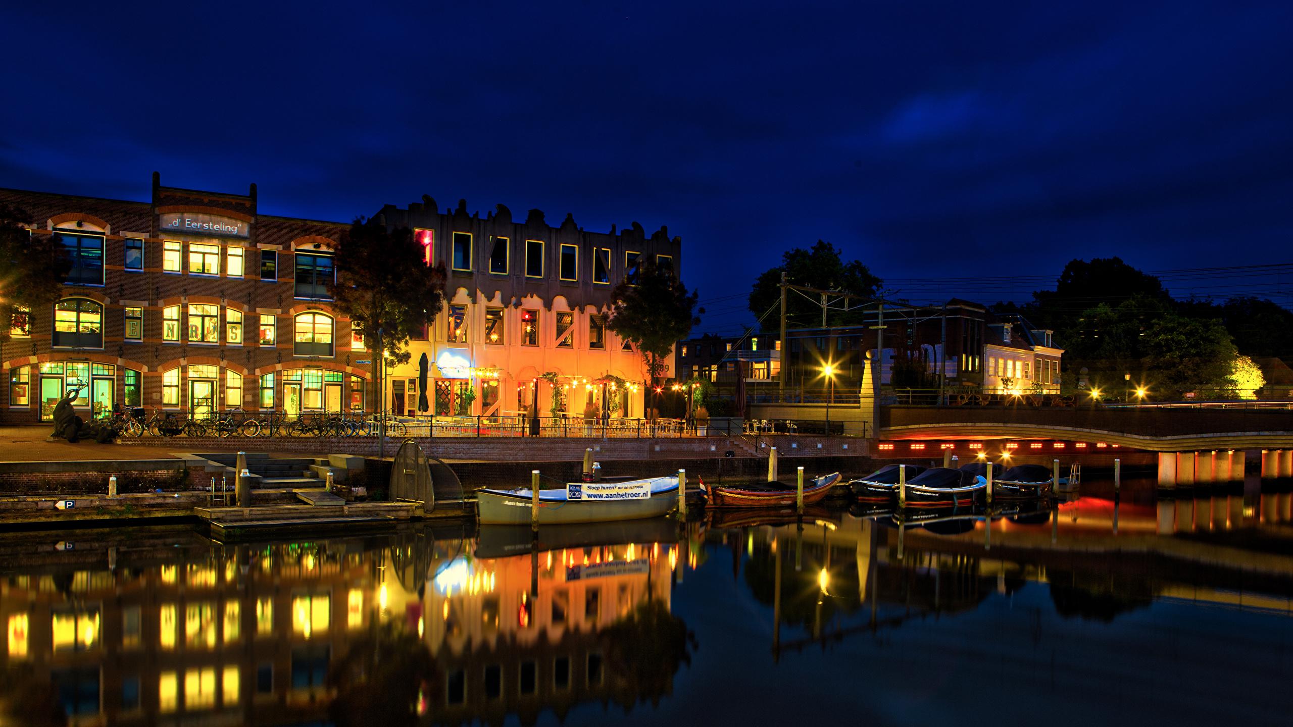 Фото Нидерланды Amersfoort canals Водный канал ночью Лодки Причалы Уличные фонари Дома город 2560x1440 голландия Ночь Пирсы в ночи Ночные Пристань Города Здания