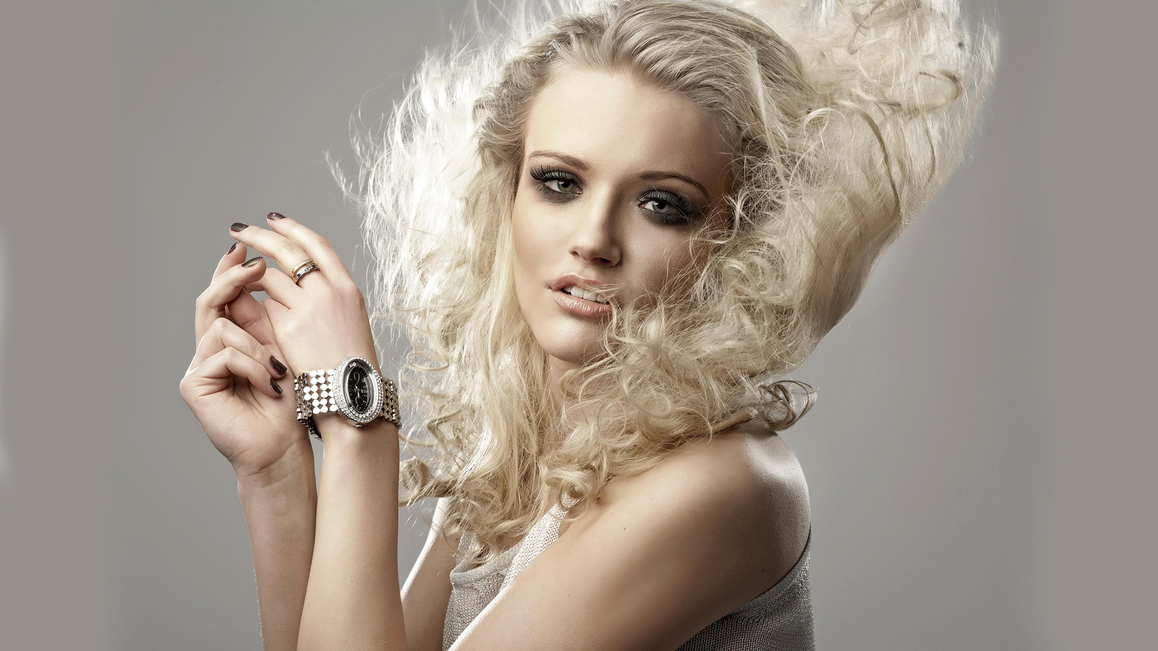 Фотография Блондинка Наручные часы Волосы молодая женщина Руки Взгляд Серый фон 3840x2160 блондинки блондинок волос девушка Девушки молодые женщины рука смотрят смотрит сером фоне