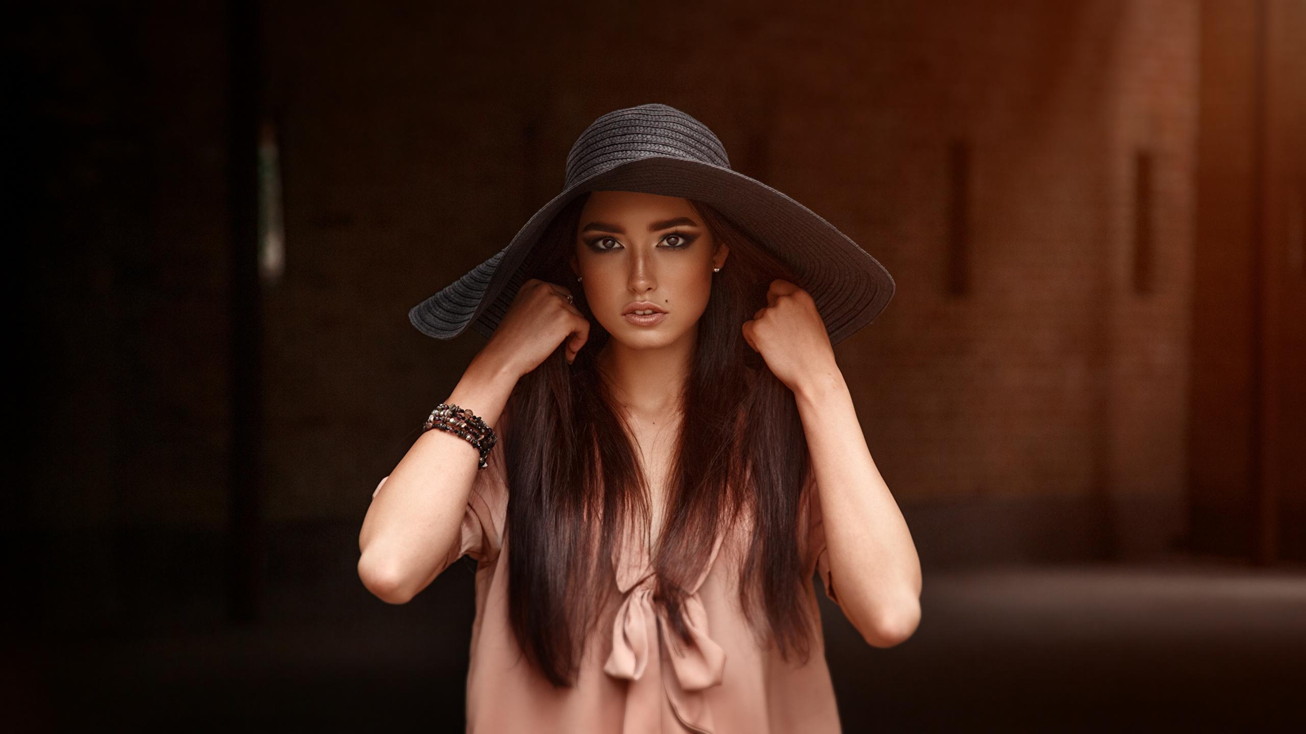 Картинка Viacheslav Krivonos фотомодель шляпы Девушки рука Взгляд 2560x1440 Модель Шляпа шляпе девушка молодая женщина молодые женщины Руки смотрит смотрят