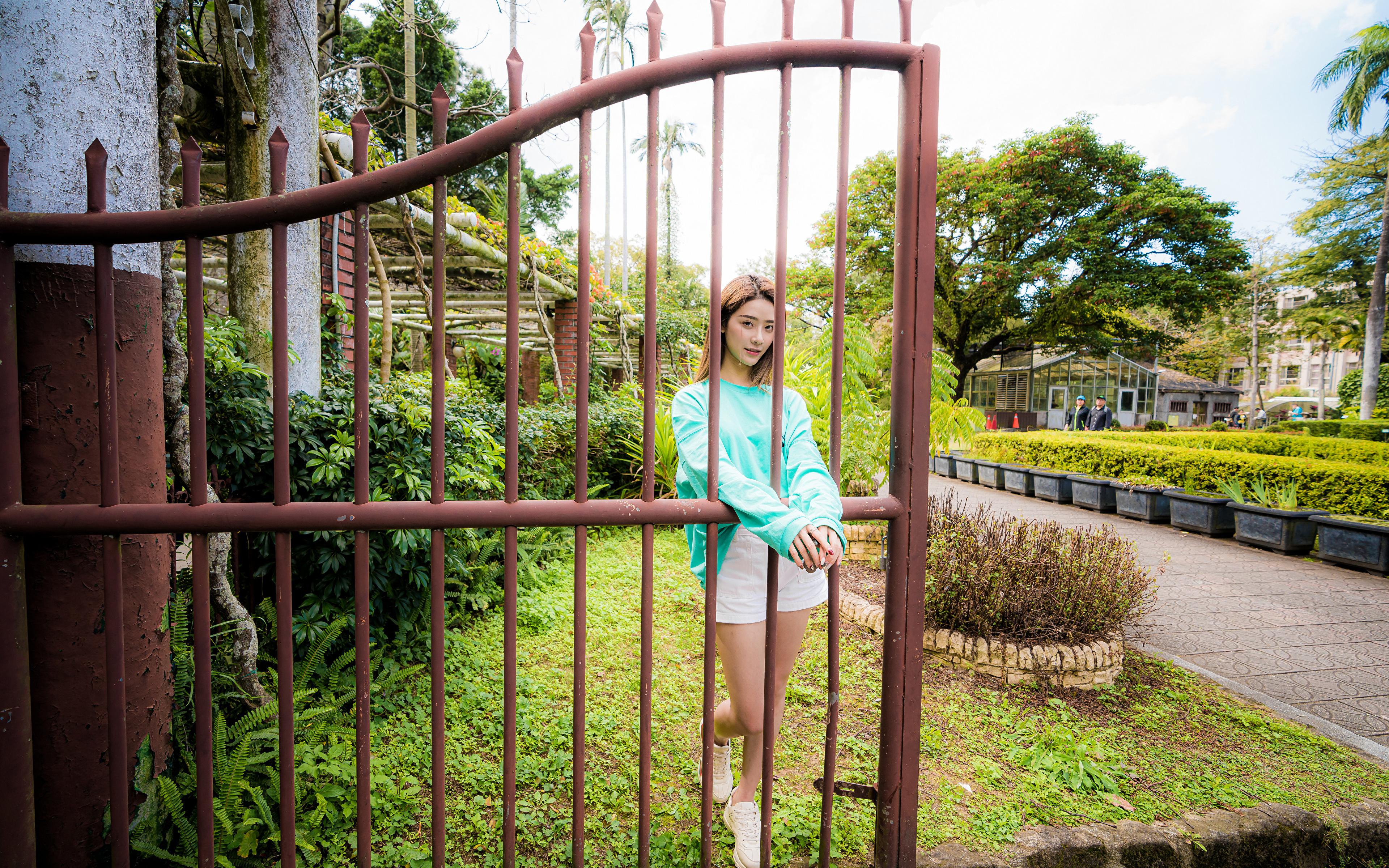 Фото позирует молодые женщины Азиаты забора 3840x2400 Поза девушка Девушки молодая женщина Забор ограда азиатки азиатка забором