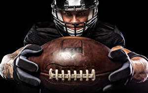 Фотографии Американский футбол Мужчины На черном фоне Униформе Мячик В шлеме спортивная