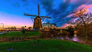 Картинка Амстердам Голландия Вечер Реки Небо Мельница Трава Природа