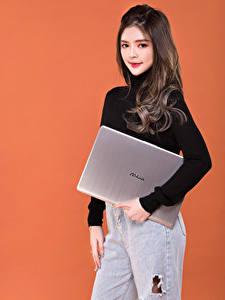 Обои Азиатки Поза Цветной фон Ноутбуки Свитере Смотрит Asus молодая женщина