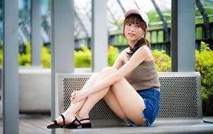 Картинка Азиатка Бейсболка Ноги Красивые Шорты Сидит Скамья Девушки