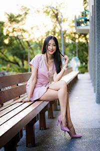 Фотографии Азиатка Скамейка Сидя Платья Ноги Улыбка Взгляд молодая женщина