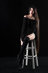 Картинка Азиатка На черном фоне Стул Сидит Сапогов Ног Свитер Волос Смотрят молодая женщина