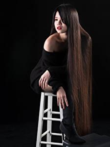 Картинки Азиатка Черный фон Стулья Сидит Сапогах Волос Мейкап Фотомодель