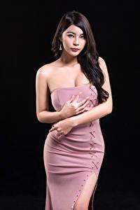 Фотография Азиатки На черном фоне Платье Руки Смотрит молодая женщина