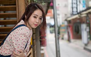 Фотография Азиаты Размытый фон Шатенка Смотрит Руки молодая женщина