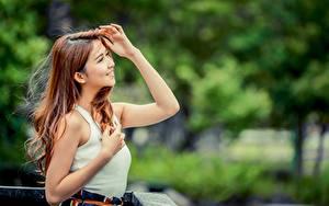 Картинки Азиаты Размытый фон Шатенка Улыбка Руки молодая женщина