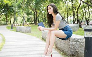 Картинки Азиатки Боке Брюнетки Юбка Руки Сидя Ноги девушка