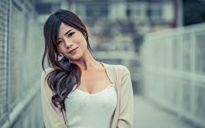 Фотографии Азиаты Размытый фон Смотрит Брюнеток молодая женщина