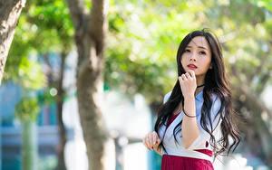 Фотографии Азиаты Размытый фон Смотрит Рука Брюнеток молодые женщины