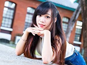 Картинка Азиатка Размытый фон Руки Лежат Смотрит Шатенки молодые женщины