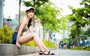 Картинка Азиатки Боке Сидящие Ног Бейсболка Смотрит девушка