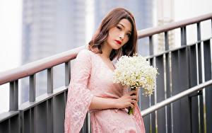 Фото Азиаты Букет Ландыши Платья Смотрят Размытый фон молодая женщина