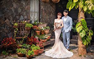 Картинка Азиаты Букет Двое Жениха Невесты Свадьба Платья Классический костюм девушка