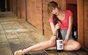 Обои Азиаты Шатенка Бутылка Сидит Рука Ног Размытый фон молодая женщина