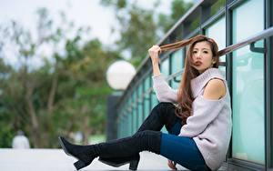 Обои для рабочего стола Азиаты Шатенки Сидит Свитере Ног Сапогов молодая женщина