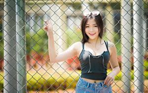Картинки Азиатки Брюнетка Очках Взгляд Улыбка Рука Забора девушка