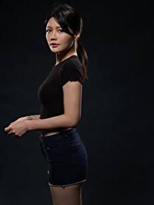Картинка Азиатка Брюнетка Шорты Руки Смотрит Черный фон молодые женщины