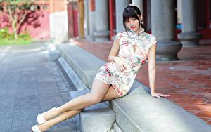 Картинки Азиатки Брюнетка Сидящие Платья Ног Смотрит девушка