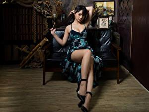 Фотография Азиатка Брюнеток Диван Сидит Платья Ног
