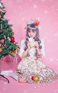 Картинка Азиаты Рождество Сидит Платье Новогодняя ёлка Шарики Цветной фон Взгляд молодые женщины