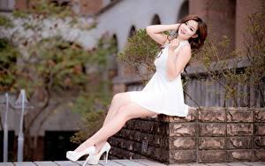 Фото Азиаты Платья Шатенки Сидящие Рука Ноги Туфлях Размытый фон девушка