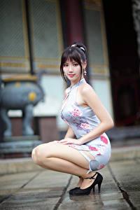 Фотографии Азиаты Платье Сидя Смотрит Боке Брюнеток молодая женщина
